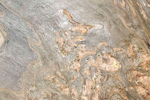 A green and peach colored granite with dark veins.