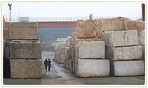 Two men stand in a canyon of quarried stone blocks